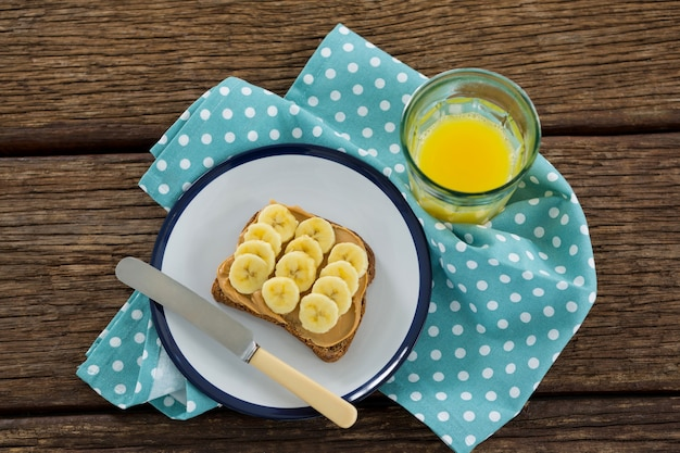 Banana cortada em fatias de pão integral em um prato com um copo de suco na mesa de madeira