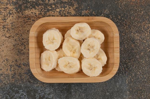 Banana cortada em fatias em prato de madeira