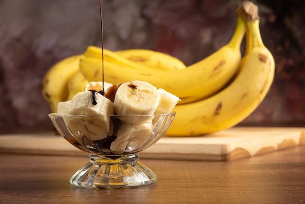 Banana cortada em fatias em uma jarra de vidro com cobertura de chocolate e mais bananas ao fundo, fundo abstrato escuro, foco seletivo.