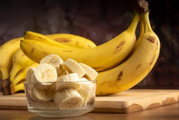 Banana cortada em fatias em uma jarra de vidro com mais bananas no fundo, fundo abstrato escuro, foco seletivo.