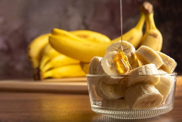 Banana cortada em fatias em uma jarra de vidro sendo banhada em mel com mais bananas no fundo, fundo abstrato escuro, foco seletivo.