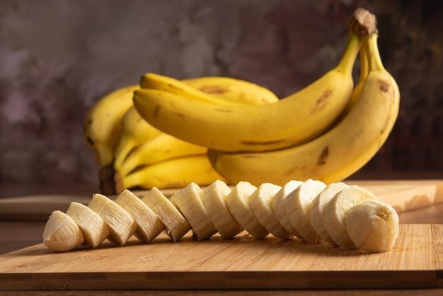 Banana cortada em fatias na madeira com mais bananas no fundo, fundo abstrato escuro, foco seletivo.