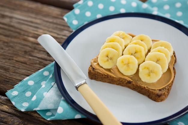 Banana cortada espalhada no pão integral no prato na mesa de madeira