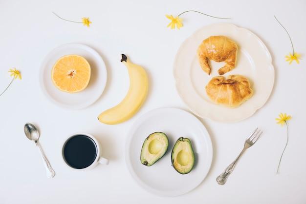 Banana; croissants; abacate cortado ao meio; xícara de café sobre fundo branco com colher e um garfo no pano de fundo branco