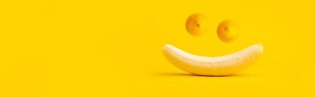 Banana descascada e dois limões no espaço amarelo, focinho sorridente engraçado