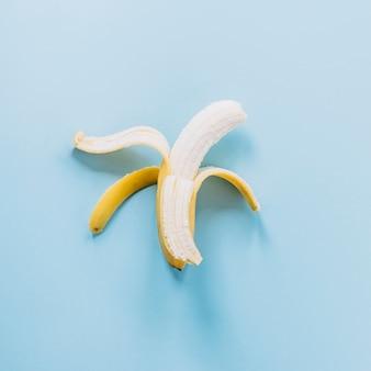 Banana descascada em fundo azul