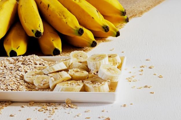 Banana e aveia em um prato e sobre a mesa