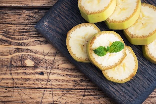 Banana e banana fatiada em pedaços com hortelã em madeira rústica. vista do topo