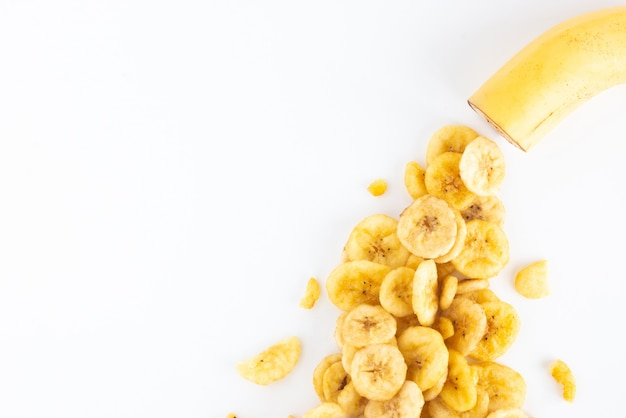 Banana e fatias de banana secas com espaço de cópia isolado no branco