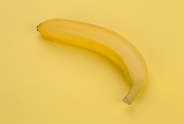 Banana em fundo amarelo. minimalismo.