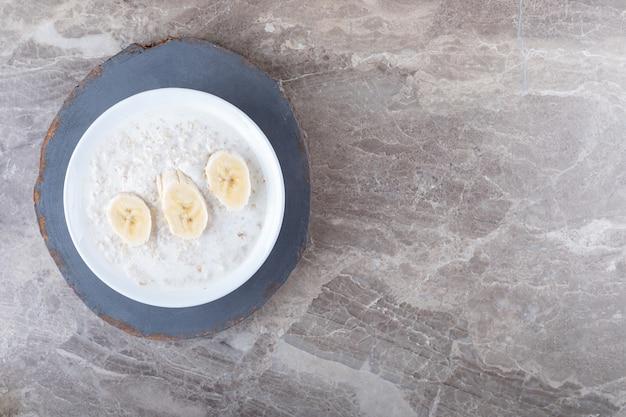 Banana fatiada em um prato de arroz, no fundo de mármore.