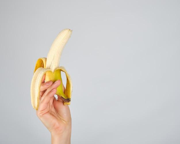 Banana fresca descascada na mão fêmea