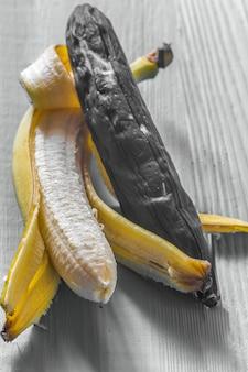 Banana fresca e podre em fundo de madeira