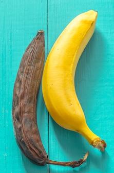Banana fresca e podre na madeira vista de cima