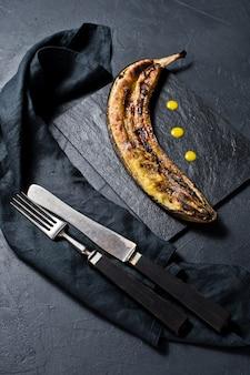 Banana frita com mel em uma placa de pedra preta.