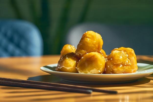 Banana frita em caramelo e bata com sementes de gergelim em um prato branco. receita e culinária chinesa