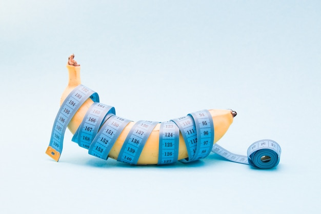 Banana madura enrolada em fita métrica azul em uma superfície azul