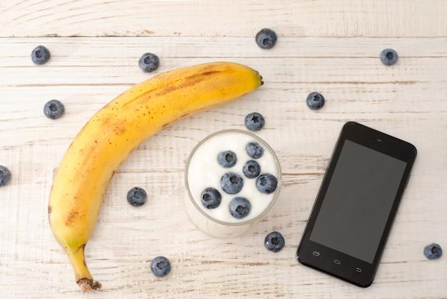 Banana madura, iogurte com amoras, smartphone e frutas, mesa de madeira clara