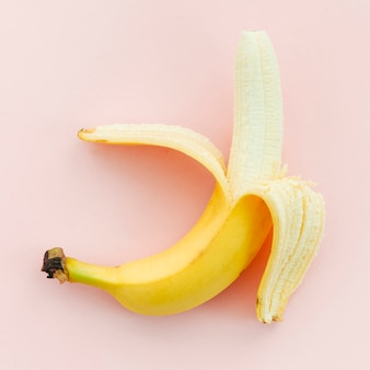 Banana meio descascada no fundo rosa