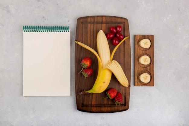 Banana, morango e frutas vermelhas em uma bandeja de madeira com um livro de recibos ao lado