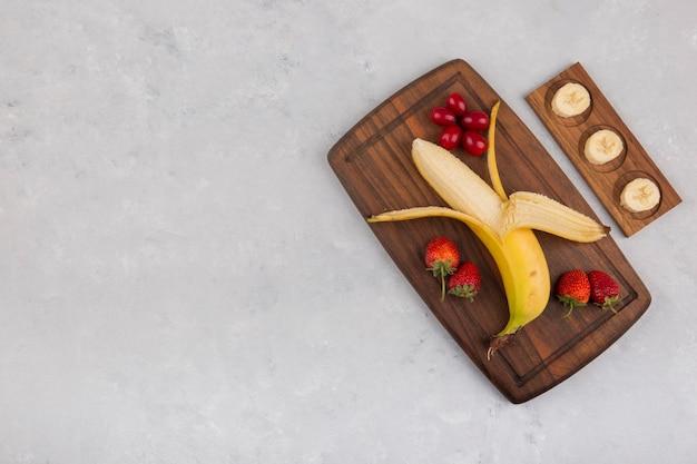Banana, morango e frutas vermelhas em uma travessa de madeira, vista superior
