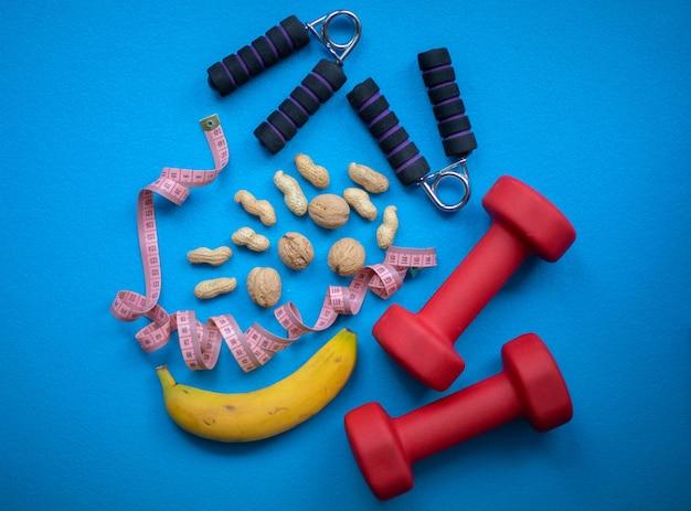 Banana, nozes, fita métrica, reforçador de pega de mão e halteres em uma parede azul. alimentos e equipamentos de fitness para um estilo de vida saudável