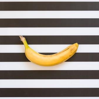 Banana orgânica na vista superior do plano de fundo com listras pretas e brancas