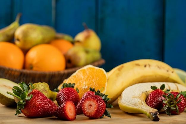 Banana, pêra fatiada, morangos e laranjas em uma parede azul