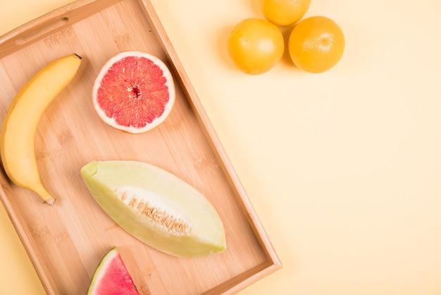Banana; toranja; melancia; e muskmelon na bandeja de madeira perto das laranjas inteiras contra o fundo bege