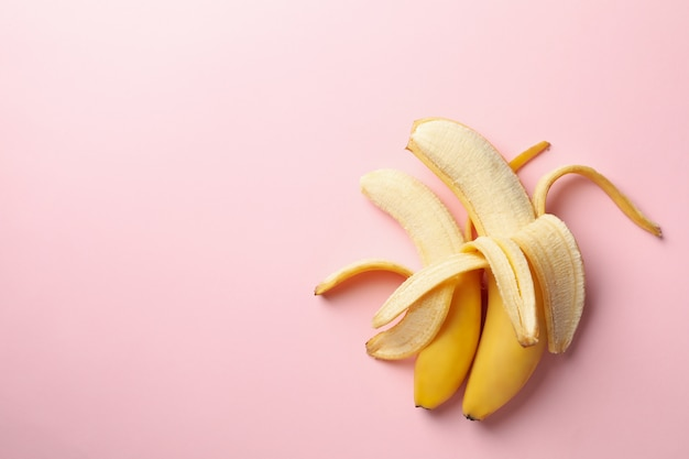 Bananas abertas em fundo rosa. fruta fresca