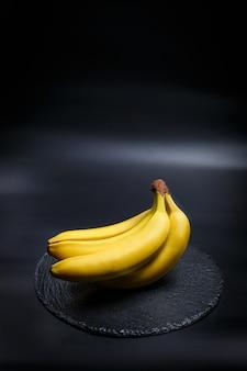 Bananas amarelas e frescas em um fundo preto