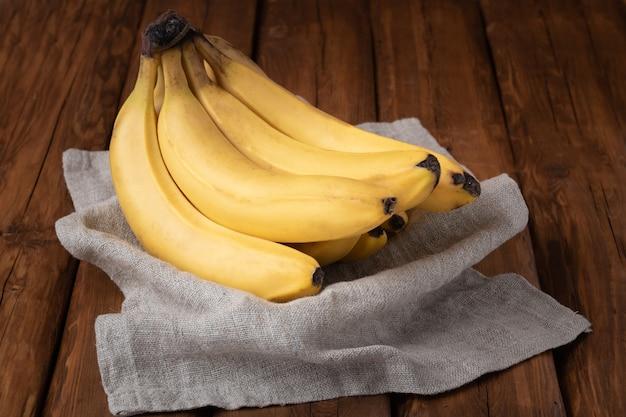 Bananas amarelas frescas em um fundo de madeira