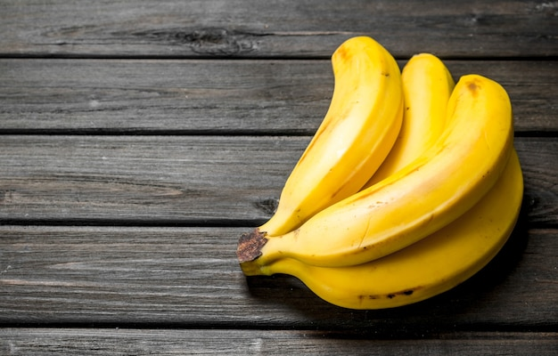 Bananas amarelas frescas. sobre um fundo preto de madeira. Foto Premium