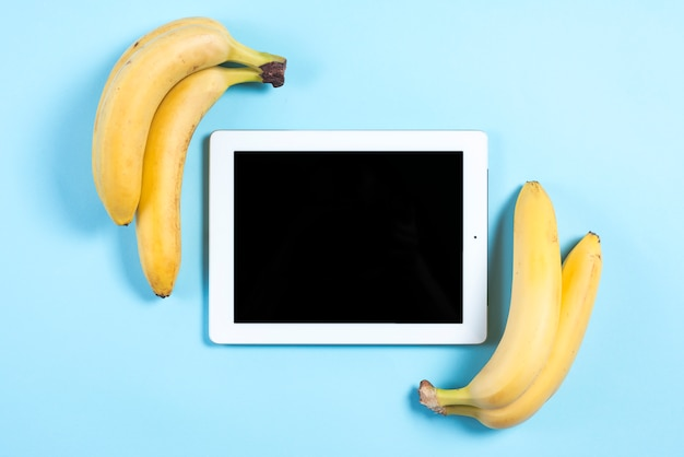 Bananas amarelas perto do tablet digital sobre fundo azul