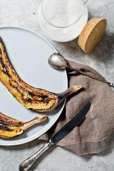 Bananas assadas com mel em um prato cinza.