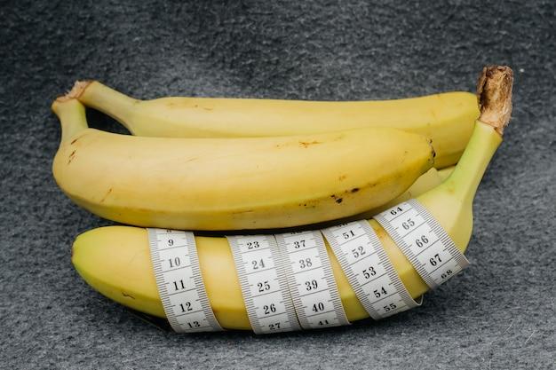 Bananas com fita para medir a forma.