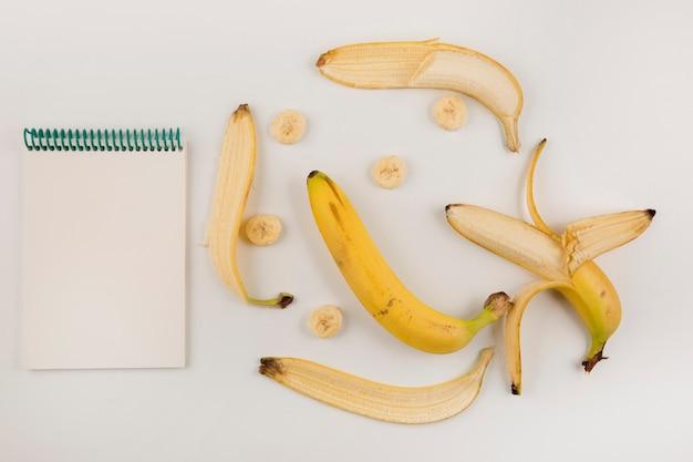 Bananas descascadas e fatiadas em fundo branco com um livro de recibos de lado