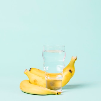 Bananas e copo de espaço de cópia de água