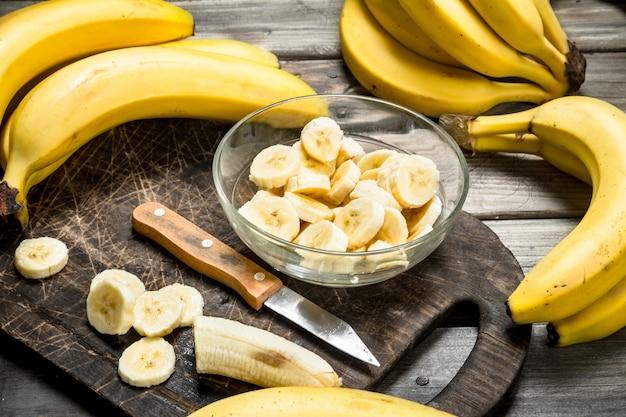 Bananas e fatias de banana em um prato em uma tábua preta com uma faca. sobre um fundo de madeira.