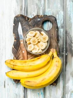 Bananas e fatias de banana em uma tigela de vidro em uma velha tábua de corte.