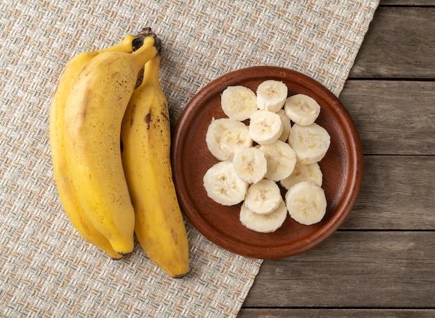 Bananas e fatias em um prato sobre uma mesa de madeira