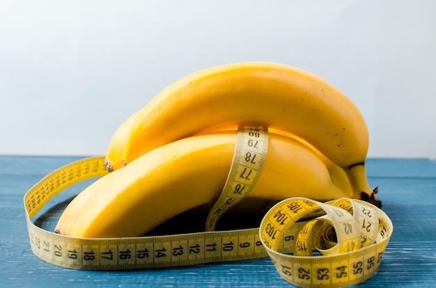 Bananas e fita centímetro está sobre uma mesa de madeira.