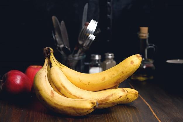 Bananas e maçãs na mesa de madeira.