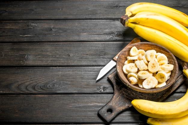 Bananas e pedaços de banana em uma placa de madeira sobre uma tábua de corte com uma faca. em uma madeira preta.