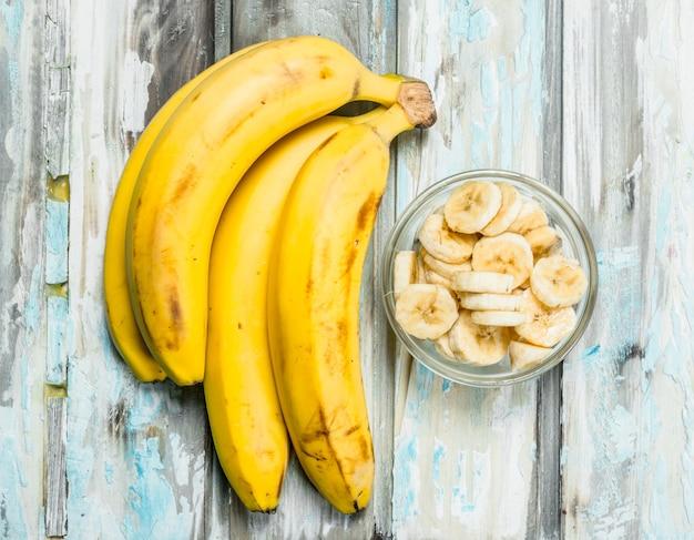 Bananas e rodelas de banana em uma tigela de vidro. sobre um fundo branco de madeira.