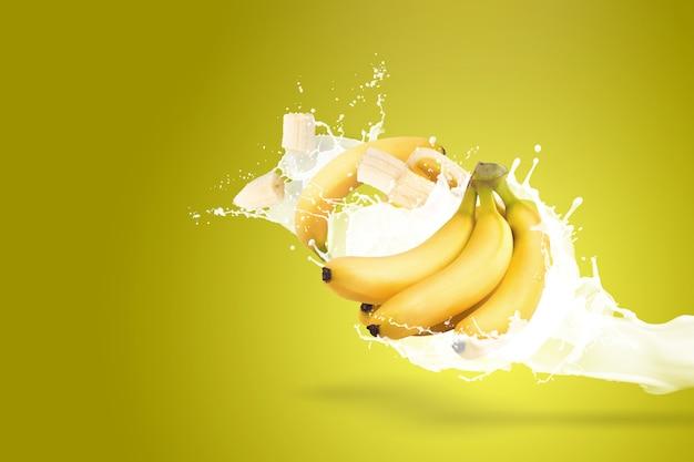 Bananas e salpicos de leite, isolados em um fundo amarelo