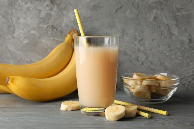 Bananas e suco contra mesa cinza. fruta fresca