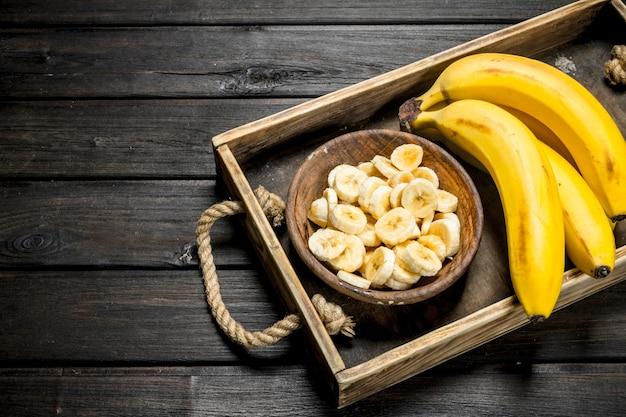 Bananas e um prato com rodelas de bananas em um molho de madeira. sobre um fundo preto de madeira.