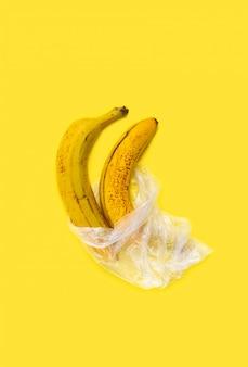 Bananas em um saco plástico em um fundo amarelo