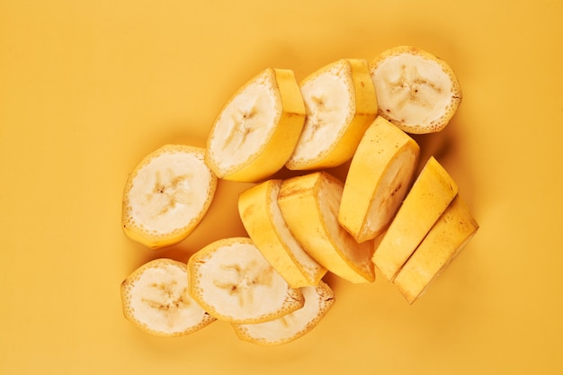 Bananas fatiadas em fundo amarelo close-up, ingrediente de sobremesa saudável